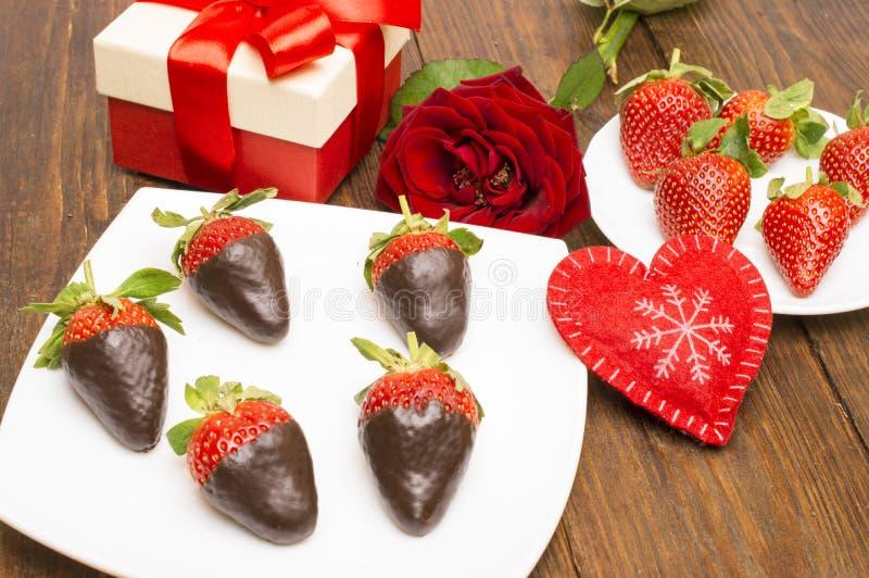 新鲜的草莓在黑暗的巧克力、礼物和心脏浸洗了在木背景 日s华伦泰 库存照片