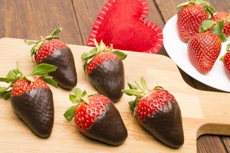 新鲜的草莓在黑暗的巧克力和心脏浸洗了在木背景 日s华伦泰 免版税图库摄影