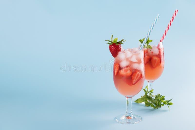新鲜的草莓夏天鸡尾酒和冰块 两块玻璃用草莓、冰和酒-在淡色蓝色的草莓桑格里酒 免版税库存照片