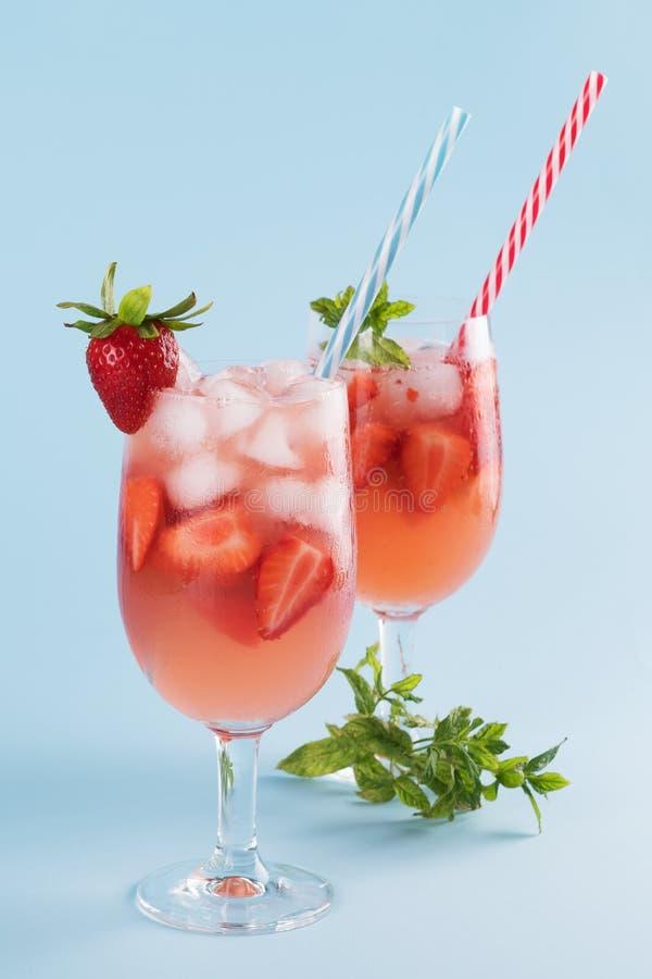 新鲜的草莓夏天鸡尾酒和冰块 两块玻璃用草莓、冰和酒-在淡色蓝色的草莓桑格里酒 图库摄影