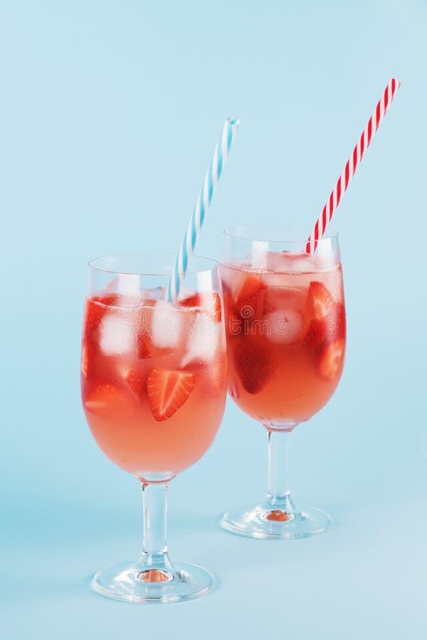 新鲜的草莓夏天鸡尾酒和冰块 两块玻璃用草莓、冰和酒-在淡色蓝色的草莓桑格里酒 免版税图库摄影