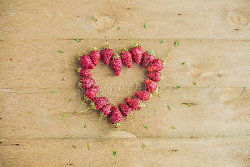 新鲜的草莓排列在老木背景的心脏形状 免版税库存照片