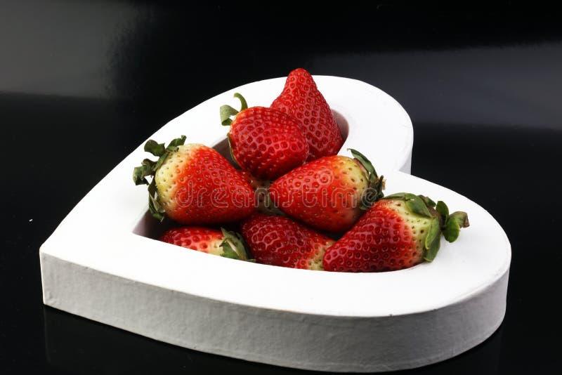 新鲜的草莓排列在老木背景的心脏形状 L 免版税库存照片