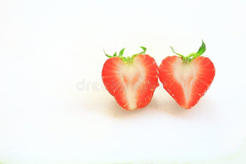 新鲜的草莓,甜果子,在白色塑料砧板、心脏和爱概念 免版税图库摄影