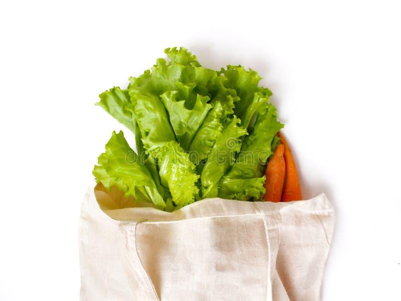 新鲜的莴苣叶子和红萝卜在一个亚麻制袋子购物的 图库摄影