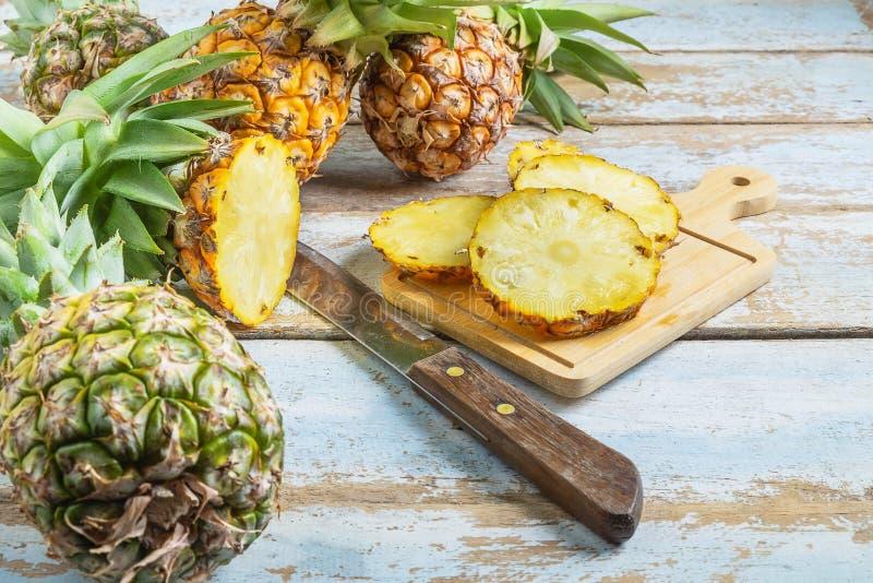 新鲜的菠萝果子切了在一个木切板的 免版税库存图片