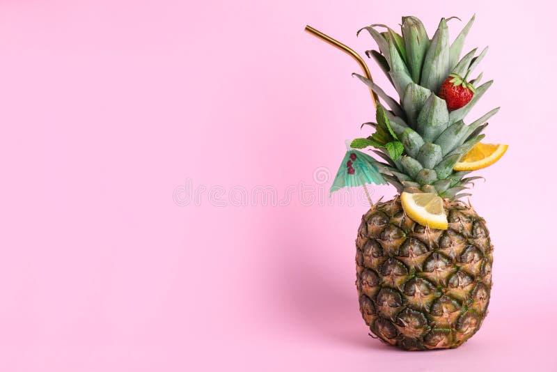 新鲜的菠萝装饰用果子和秸杆当在颜色背景的夏天鸡尾酒 免版税库存照片