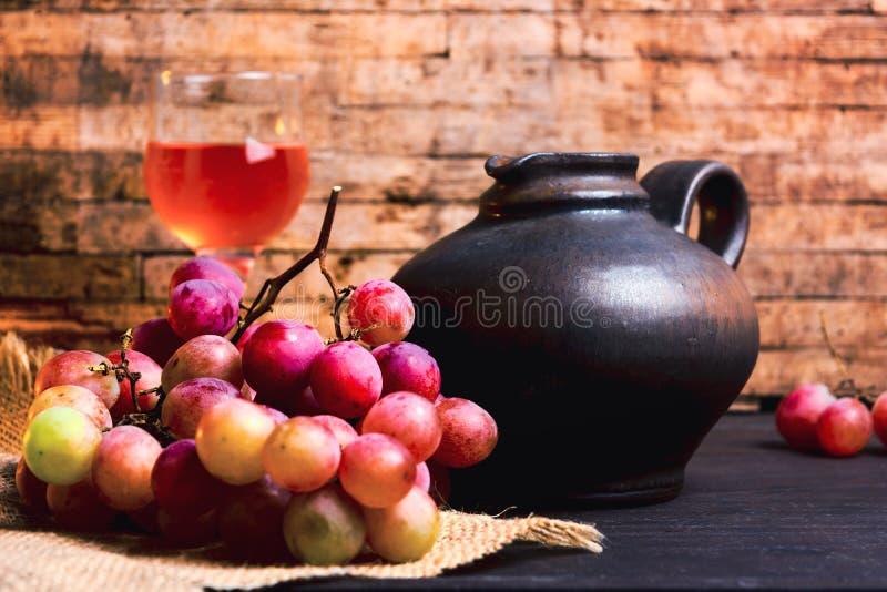 新鲜的葡萄和自创酒在桌上 免版税图库摄影