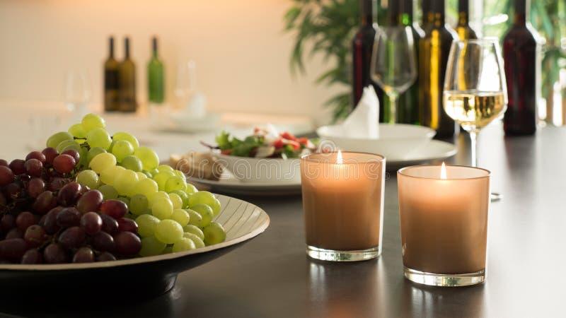 新鲜的葡萄和被点燃的蜡烛在餐馆冲击与酒杯和酒瓶 免版税库存图片