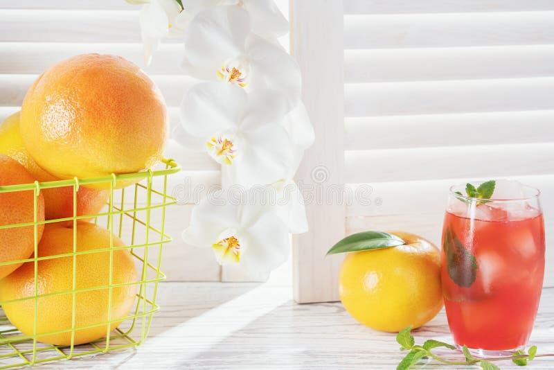 新鲜的葡萄柚和杯与冰的葡萄柚汁在土气白色木桌上 免版税库存图片
