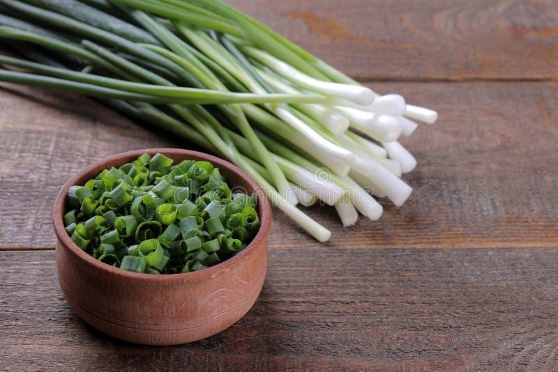 新鲜的葱和一个木碗用切的葱在一张棕色木桌上 库存照片