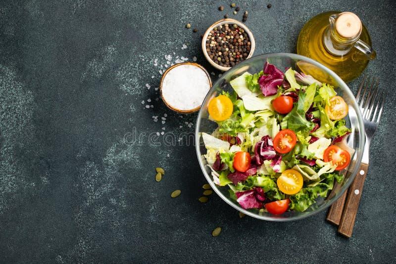 新鲜的蕃茄、黄瓜、葱、菠菜、莴苣和南瓜籽健康菜沙拉在碗 饮食菜单 与警察的顶视图 库存照片