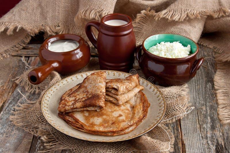 新鲜的薄煎饼,在木桌上的乳制品 免版税库存图片