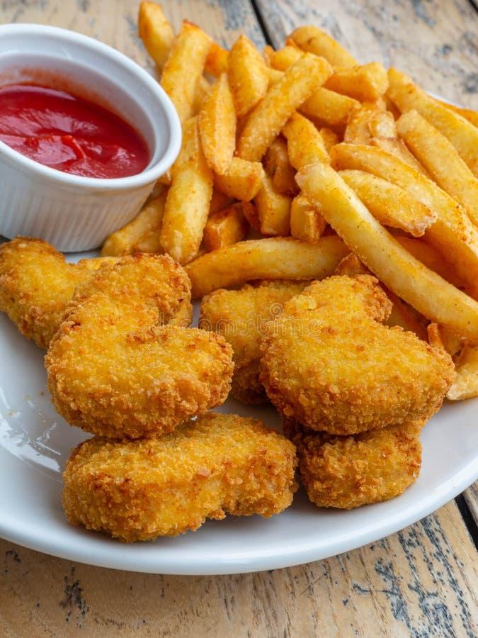 新鲜的薯条和鸡块服务用在木桌上的西红柿酱 图库摄影
