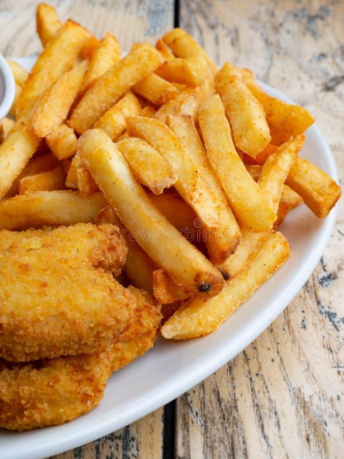 新鲜的薯条和鸡块服务用在木桌上的西红柿酱 免版税图库摄影