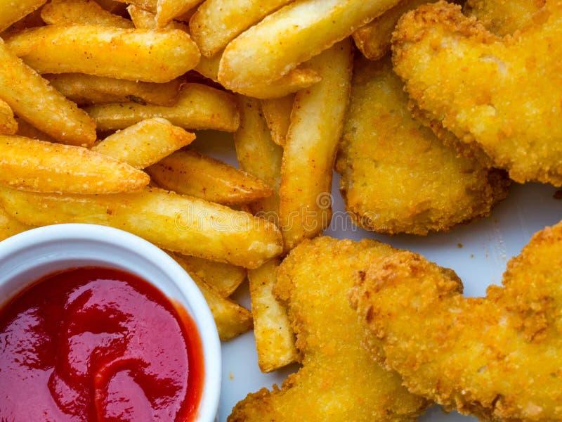 新鲜的薯条和鸡块服务用在白色板材的西红柿酱 免版税库存照片