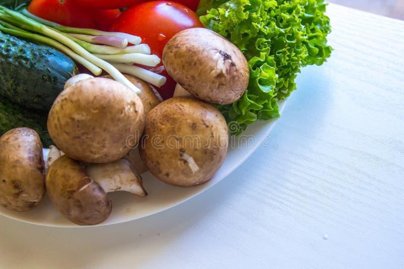 新鲜的蘑菇和菜板材  免版税库存照片