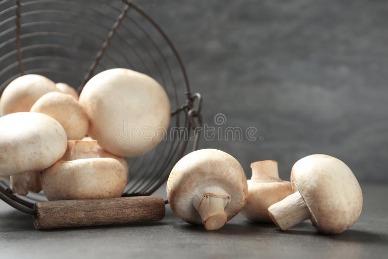 新鲜的蘑菇蘑菇和金属篮子在桌上 免版税库存照片
