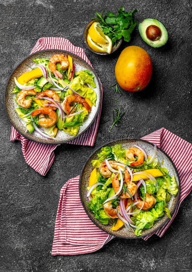 新鲜的虾、芒果鲕梨莴苣沙拉、橄榄油和柠檬选矿 健康的食物 顶视图,灰色背景 免版税库存照片