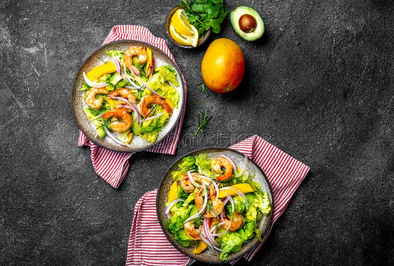 新鲜的虾、芒果鲕梨莴苣沙拉、橄榄油和柠檬选矿 健康的食物 顶视图,灰色背景 库存照片
