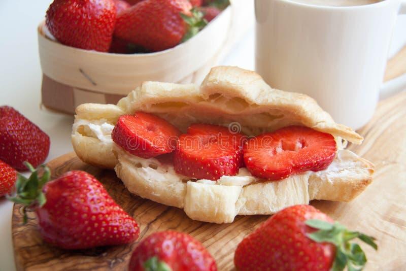 新鲜的被烘烤的新月形面包用草莓 免版税库存照片