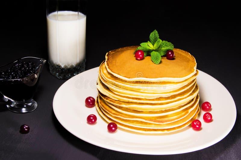 新鲜的被烘烤的薄煎饼可口早餐用牛奶、蓝莓果酱和新鲜的蔓越桔 库存图片