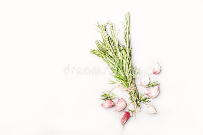 新鲜的迷迭香和红色大蒜在白色香料食物背景,顶视图 免版税库存图片