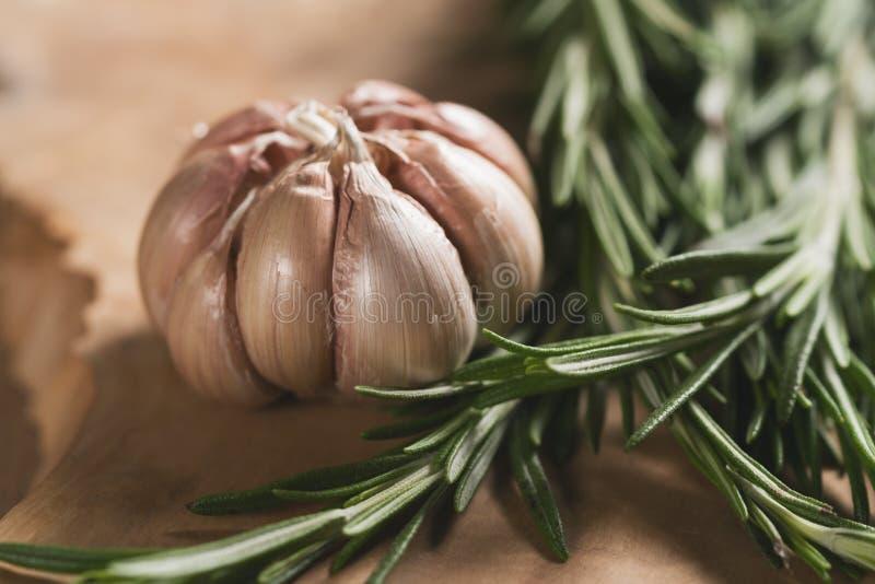 新鲜的迷迭香束和大蒜在木委员会 免版税库存照片
