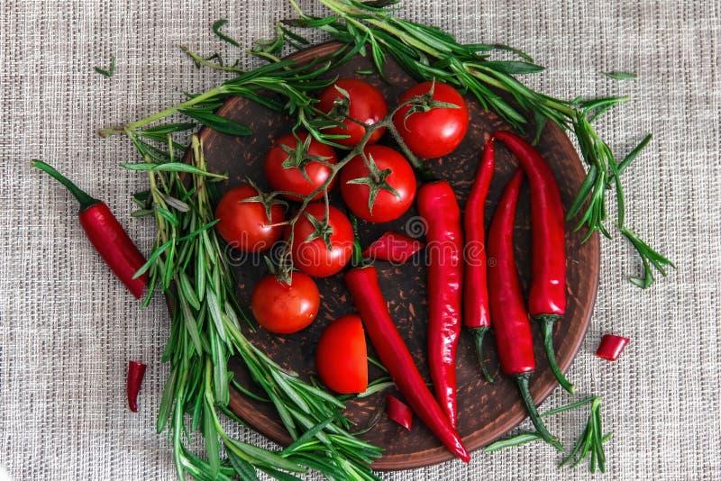 新鲜的迷迭香西红柿、小树枝和在黏土板材的辣椒在桌上 新鲜蔬菜、的草本和的香料- 免版税库存照片