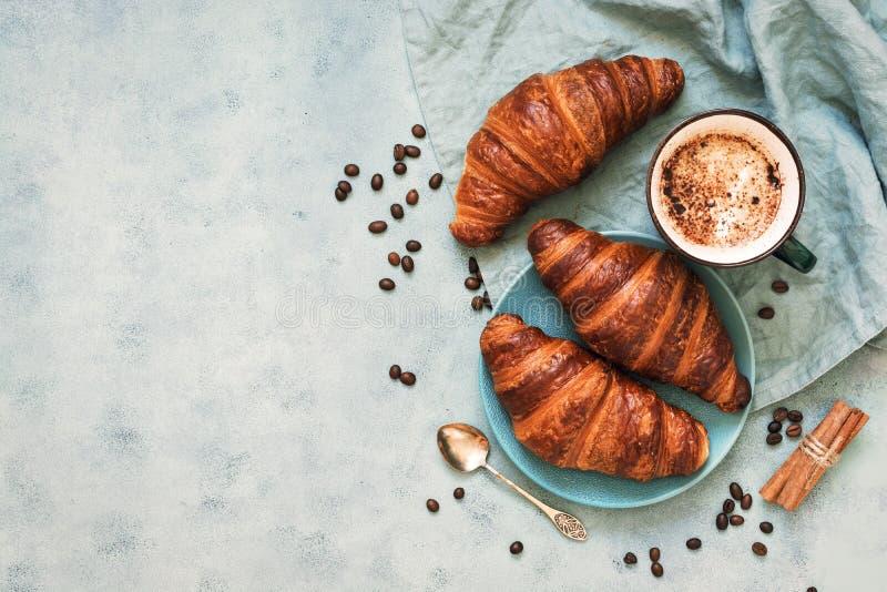 新鲜的酥皮点心和咖啡与泡沫洒与可可粉 法国小圆面包 顶视图,蓝色背景,拷贝空间 免版税图库摄影