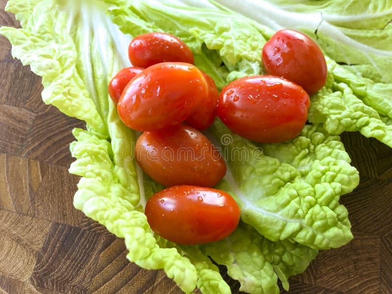 新鲜的酥脆中国叶子圆白菜沙拉用在一张木桌上的李子西红柿 免版税库存图片