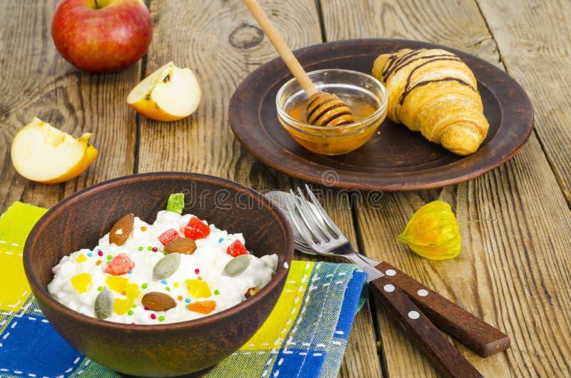 新鲜的酸奶干酪用脯和坚果,蜂蜜,午餐的新月形面包 库存照片