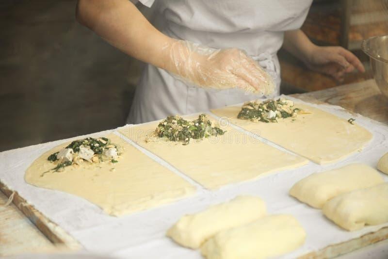 新鲜的面团和面粉,厨师的手揉比萨或饼 免版税库存照片