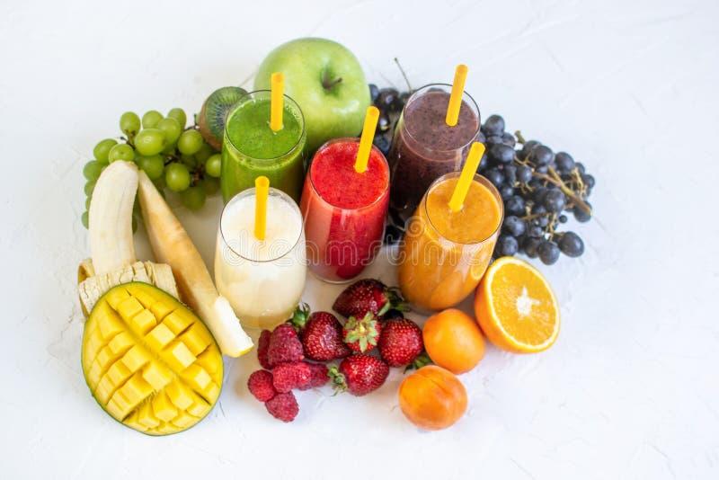 新鲜的颜色汁液圆滑的人绿色黄色红色桔子紫罗兰色白色热带水果 免版税图库摄影