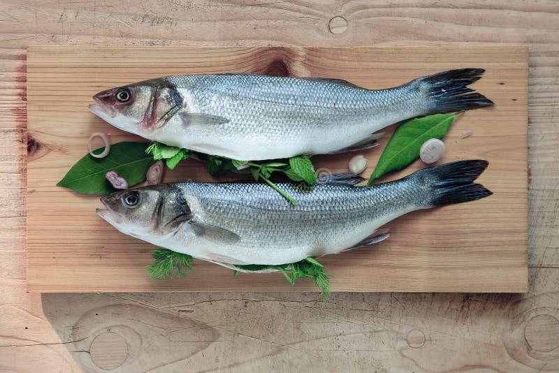 新鲜的鲈鱼整个,用草本喜欢莳萝和月桂树,土气食物摄影 免版税图库摄影