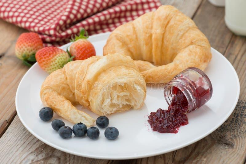 新鲜的鲜美新月形面包用果酱和莓果,草莓 免版税图库摄影