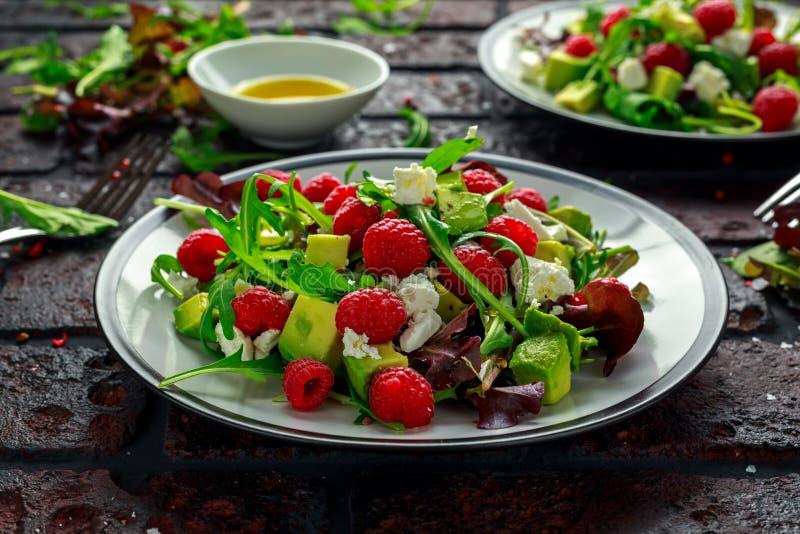 新鲜的鲜美莓沙拉用鲕梨、绿色菜、坚果、希腊白软干酪、橄榄油和草本 健康的食物 免版税库存图片