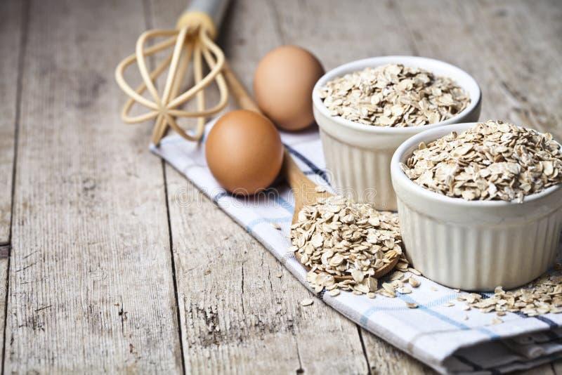 新鲜的鸡鸡蛋、燕麦剥落在陶瓷碗和木匙子在土气木桌背景 免版税库存照片