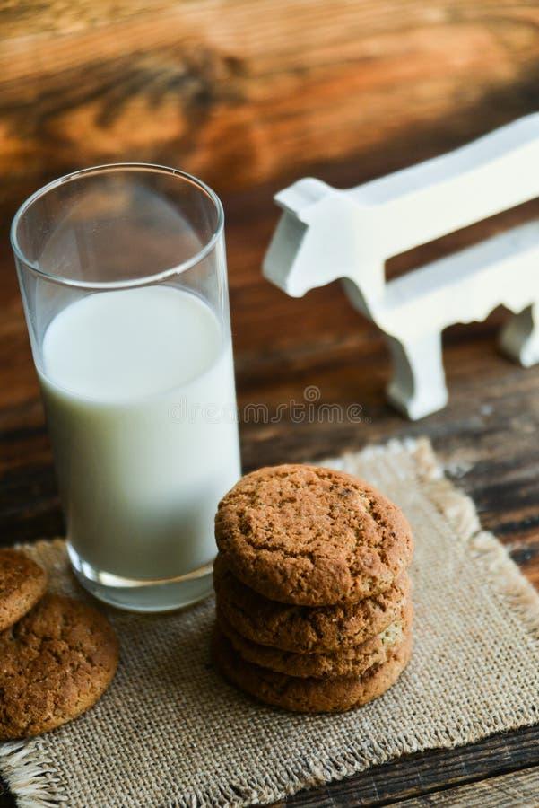 新鲜的麦甜饼和牛奶在木背景与燕麦钉  免版税库存照片