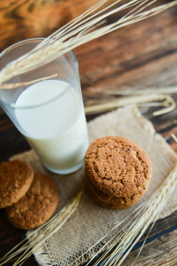 新鲜的麦甜饼和牛奶在木背景与燕麦钉  免版税图库摄影