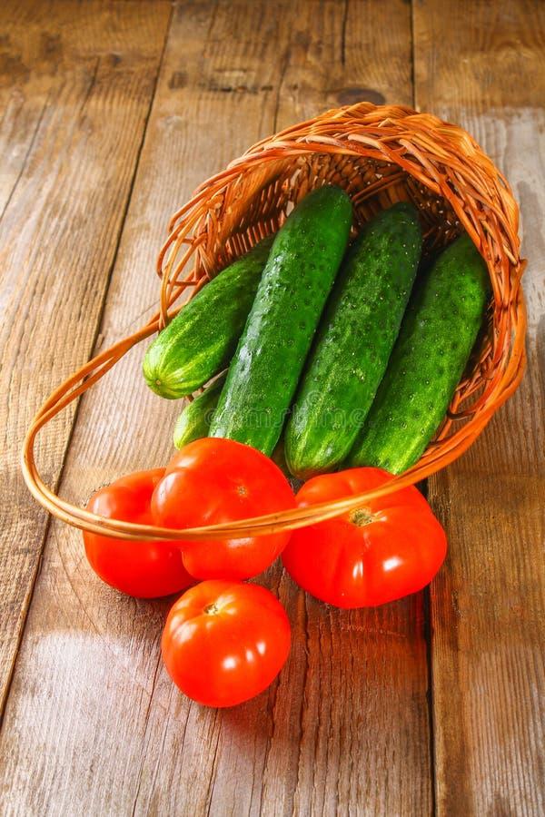 新鲜的黄瓜和蕃茄在一个篮子在一张老木桌上 库存图片