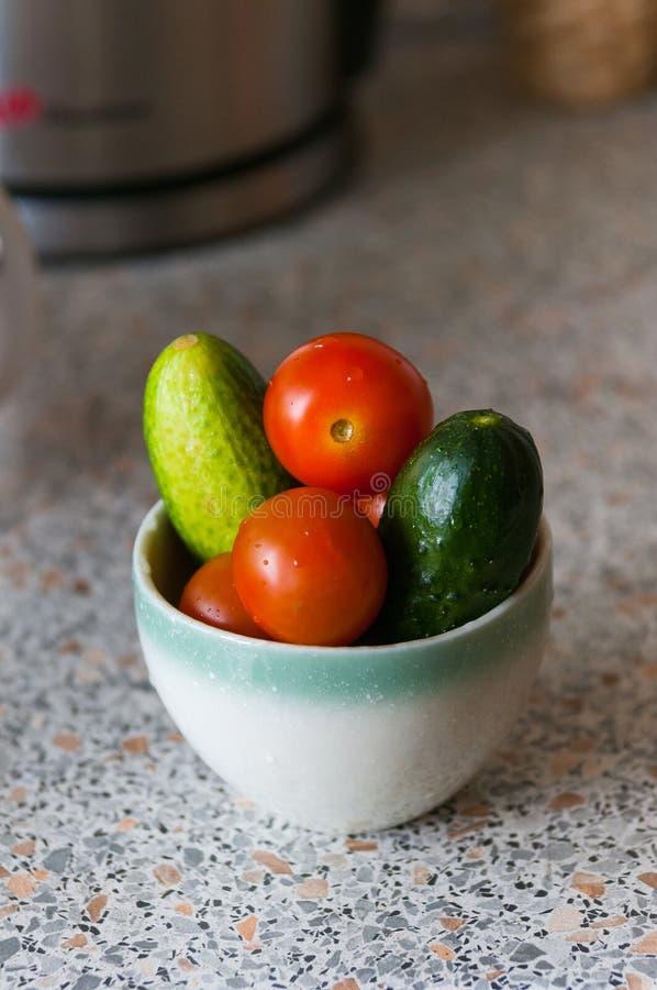 新鲜的黄瓜和蕃茄在一块玻璃在桌上 库存照片