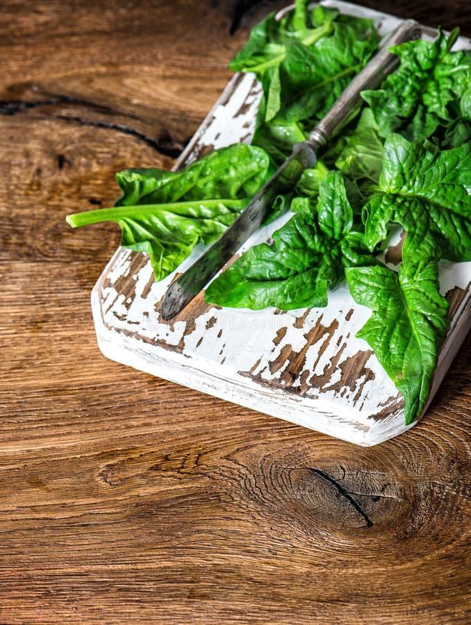 新鲜的绿色菠菜离开土气木背景 免版税库存照片