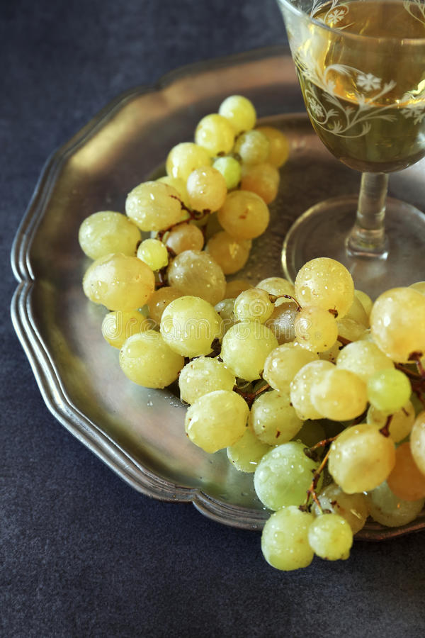 新鲜的绿色葡萄和杯白葡萄酒 库存图片