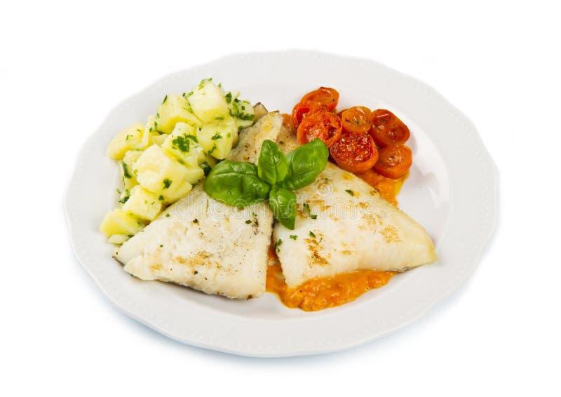 新鲜的黑鳕鱼白色盘用土豆 免版税库存照片