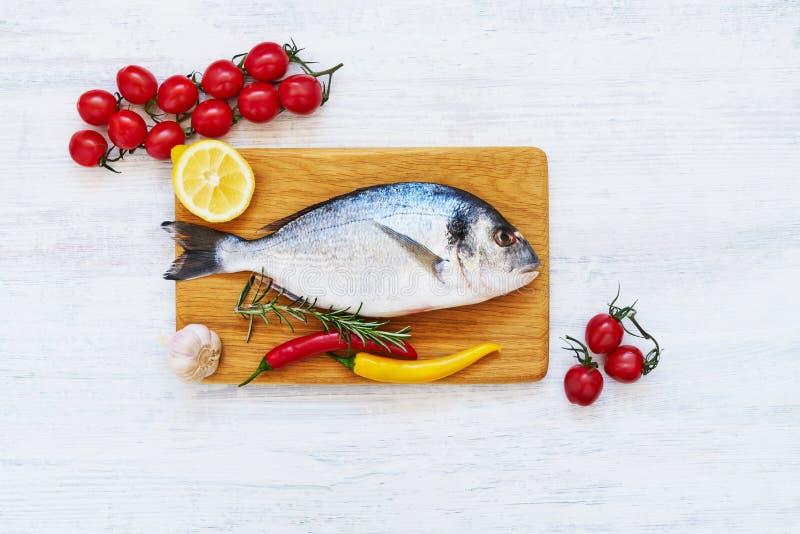 新鲜的dorada鱼用在木切板的香料 健康概念的食物 顶视图,拷贝空间 图库摄影