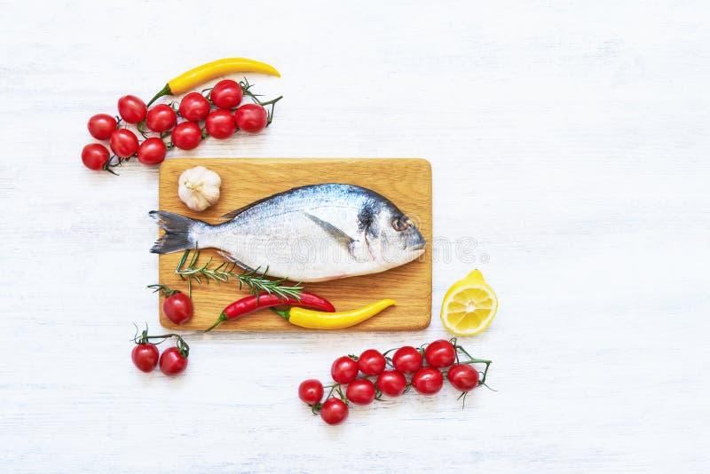 新鲜的dorada鱼用在木切板的香料 健康概念的食物 顶视图,拷贝空间 免版税库存照片