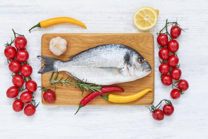 新鲜的dorada鱼用在木切板的香料 r r 图库摄影