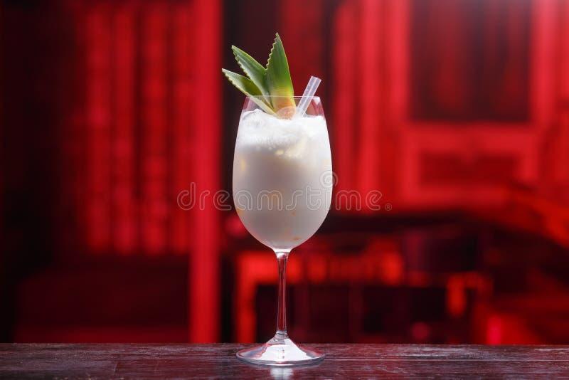 新鲜的pina colada鸡尾酒用在木柜台的椰奶,隔绝在红色被弄脏的轻的背景 免版税库存照片