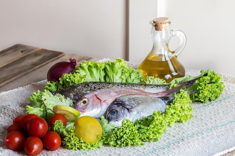 新鲜看见低音和海鲷与有些成份在蔬菜沙拉在木背景 库存图片